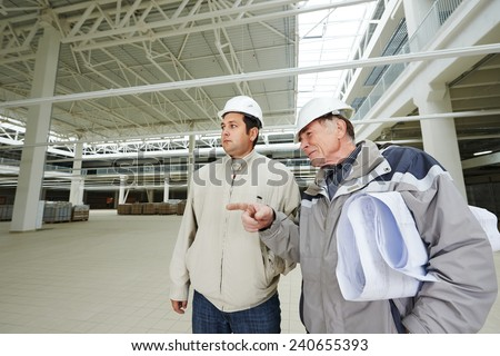 Architect and engineer worker with blueprints in a building under construction - stock photo