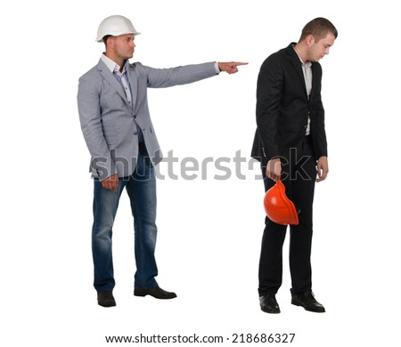 Architect , builder or engineer admonishing his young partner pointing the finger of blame at him as he turns away dejectedly - stock photo