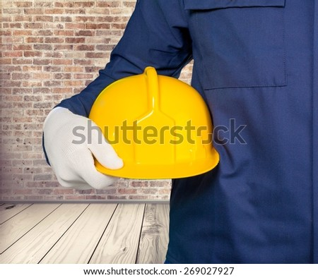 Architect. Builder with yellow hardhat and gloves, selective focus - stock photo