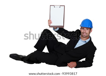 Architect casually laying on floor with clip-board - stock photo