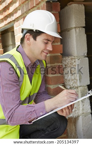 Architect Checking Insulation During Construction Project - stock photo