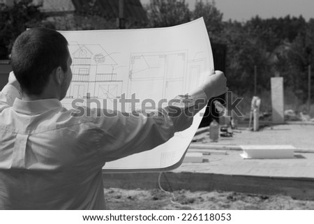 Architect checking the progress of a new build construction holding up his blueprint in front of him, monochrome image - stock photo