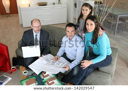 Architect discussing a project with a young family - stock photo