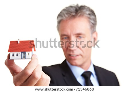 Architect holding a small house in his hand - stock photo