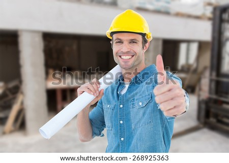 Architect holding blueprint while gesturing thumbs up against workshop - stock photo