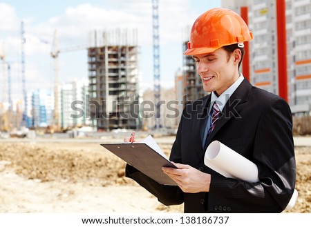 Architect in helmet writing something near  new building - stock photo