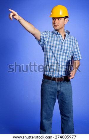 Architect in yellow hardhat holding clipboard and pointing - stock photo