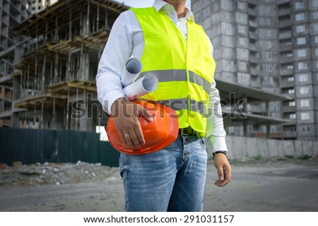 Architect in yellow safety jacket posing with red helmet at construction site - stock photo