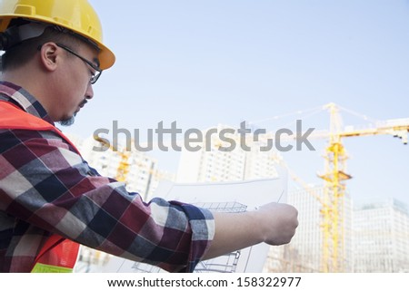 Architect looking at blueprint at construction site - stock photo