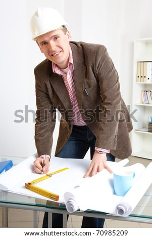 Architect looking working in office at desk. Wearing hardhat and taking notes on papers. - stock photo