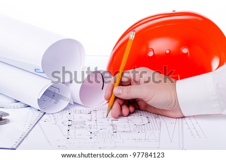 Architect makes changes to the documentation on the construction site - stock photo