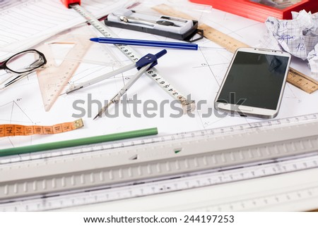 architect messy table with drawing tools - stock photo