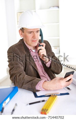 Architect on the phone calculating costs using modern smartphone, working in office at desk. Wearing helmet. - stock photo