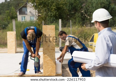 Architect or engineer on a building site watching workmen assembling prefabricated wall panels on a new build house - stock photo