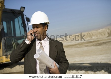 Architect phoning at construction site - stock photo