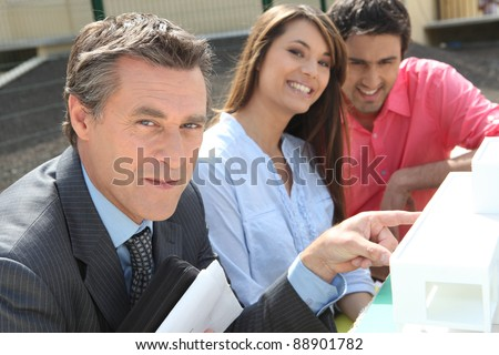 Architect presenting his model to an interested couple - stock photo