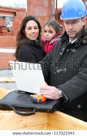 Architect reviewing digital technical drawings for his client - stock photo