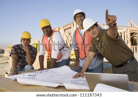 Architect showing blueprint to workers at construction site - stock photo