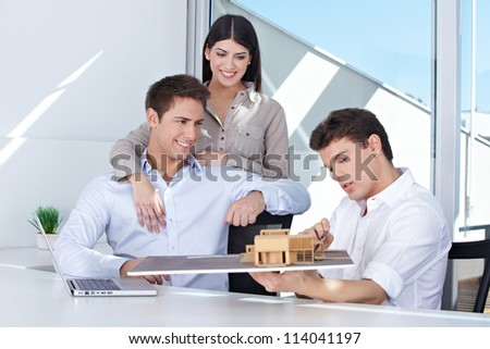 Architect showing house model to smiling couple in his office - stock photo