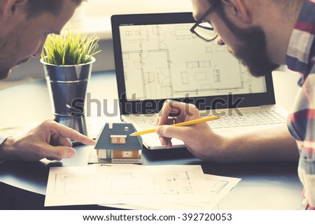 architect showing new family house model to customer at office - stock photo