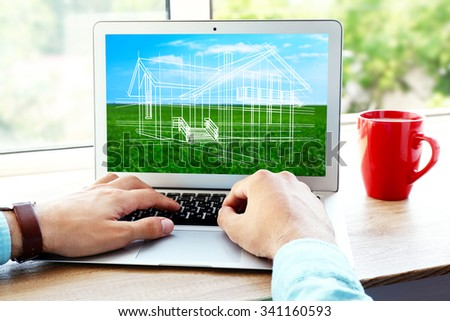 Architect showing new house project on laptop, close up - stock photo