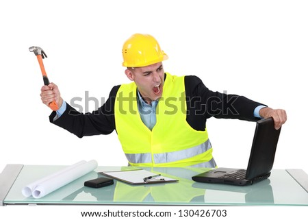 Architect smashing his laptop with hammer - stock photo