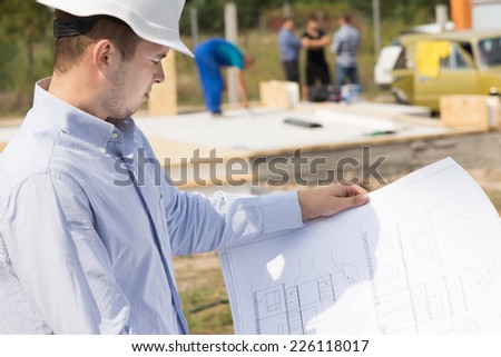 Architect standing studying a handheld blueprint on a construction site of a new build house - stock photo