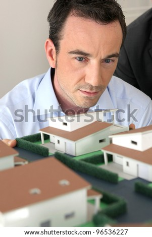 Architect staring at a model - stock photo