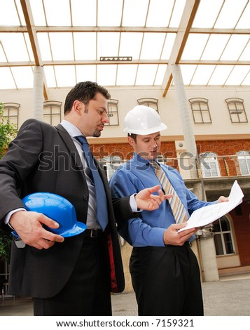 architect talking to investor over the blueprints - stock photo