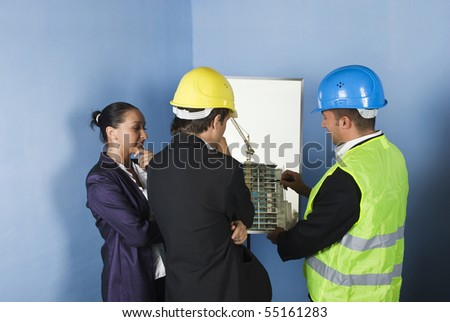 Architect team make a  presentation of architecture project and an engineer showing with pencil on graphic to his colleagues and all have a conversation in a office - stock photo