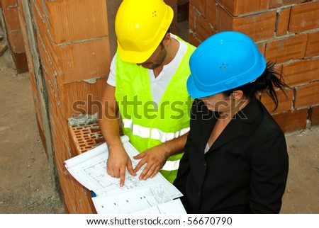 Architect team with projects having a conversation and  the man pointing on plan and showing something to his colleague woman - stock photo
