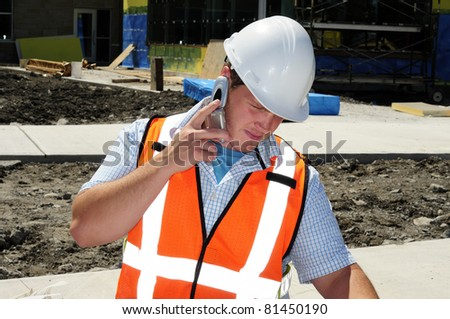 Architect Using His Mobile Cellphone On Site Checking Drawings And Specifications - stock photo