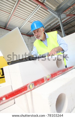 Architect using laptop computer on construction site - stock photo