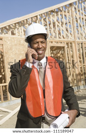 Architect wearing vest as he's on call at construction site - stock photo