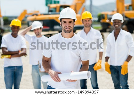 Architect with a group at a construction site holding blueprints  - stock photo