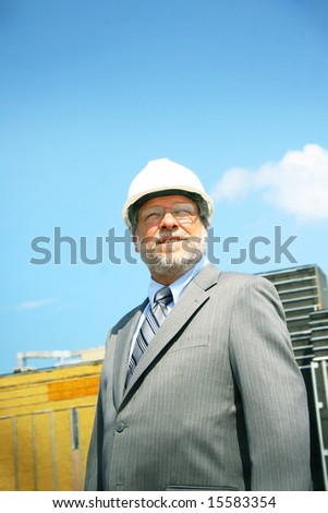Architect with white hard hat and a building in background - stock photo