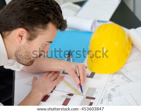 Architect working on his projects papers with compass - stock photo