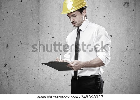 Architect writing on a clipboard on construction site - stock photo