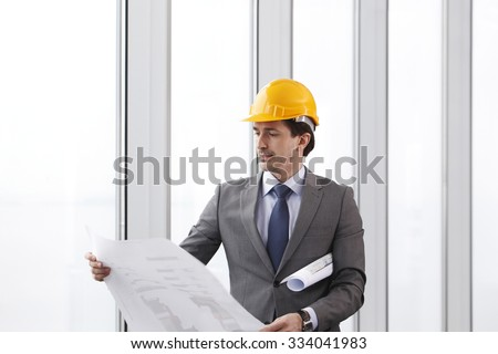 Architector in hardhat and business suit with construction plans - stock photo
