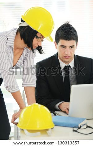 Architects having discussion about new business project using laptop - stock photo