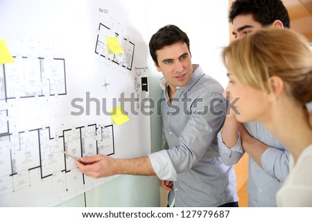 Architects in office looking at construction project - stock photo