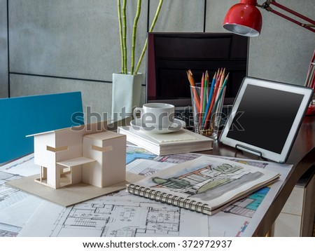 Architects & Interior designer workspace with small house model, blue print drawing/ home renovation concept - stock photo