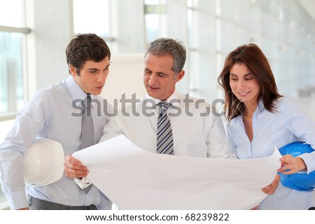 Architects meeting in hall with construction plan - stock photo