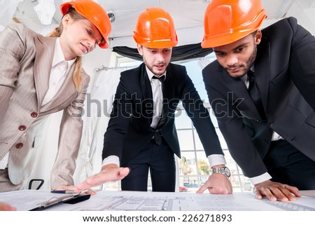 Architects next project. Three businessmen architect met in the office to discuss business projects. Successful young people in the construction helmets are on the table - stock photo