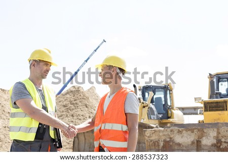 Architects shaking hands at construction site against clear sky - stock photo