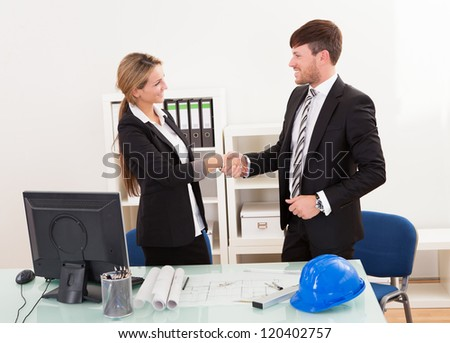Architects shaking hands in the office after reaching agreement - stock photo