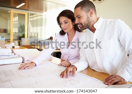 Architects Studying Plans In Modern Office Together - stock photo