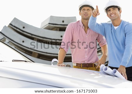 Architects with blueprints on car discussing at construction site - stock photo
