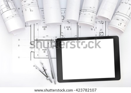 architects work table with technical drawings, tablet computer and drawing instruments - stock photo