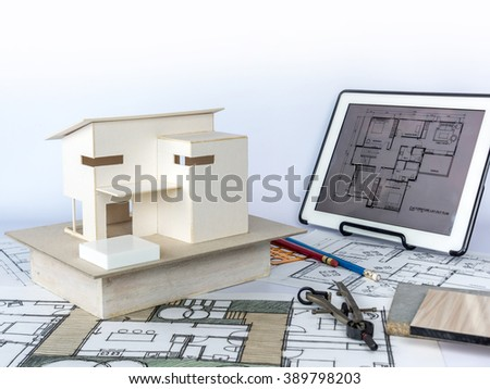 Architects workspace  with small house model, drawing, tablet &, blueprints/ home renovation concept - stock photo